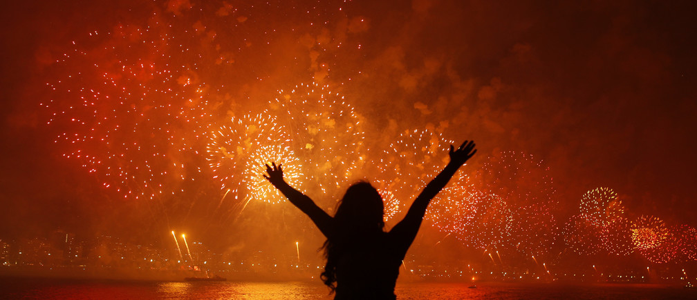 A woman celebrates the New Year as she watches fireworks exploding above Copacabana beach in Rio de Janeiro January 1, 2013. More than two million people gathered along Rio's most famous beach to witness the 20-minute display and celebrate the beginning of a new year. REUTERS/Pilar Olivares (BRAZIL - Tags: ANNIVERSARY SOCIETY TPX IMAGES OF THE DAY)   FOR BEST QUALITY IMAGE: ALSO SEE GF2E96N16UJ01. - GM1E9110V2601