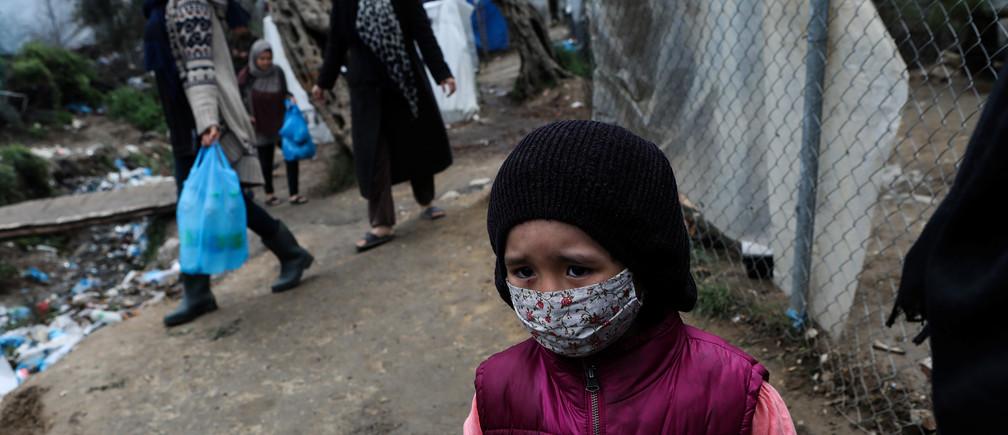Une jeune fille porte un masque de protection dans un camp de fortune pour réfugiés et migrants situé à côté du camp de Moria, lors d'un confinement national visant à contenir la propagation de la maladie à coronavirus (COVID-19), sur l'île de Lesbos, en Grèce, le 2 avril 2020.