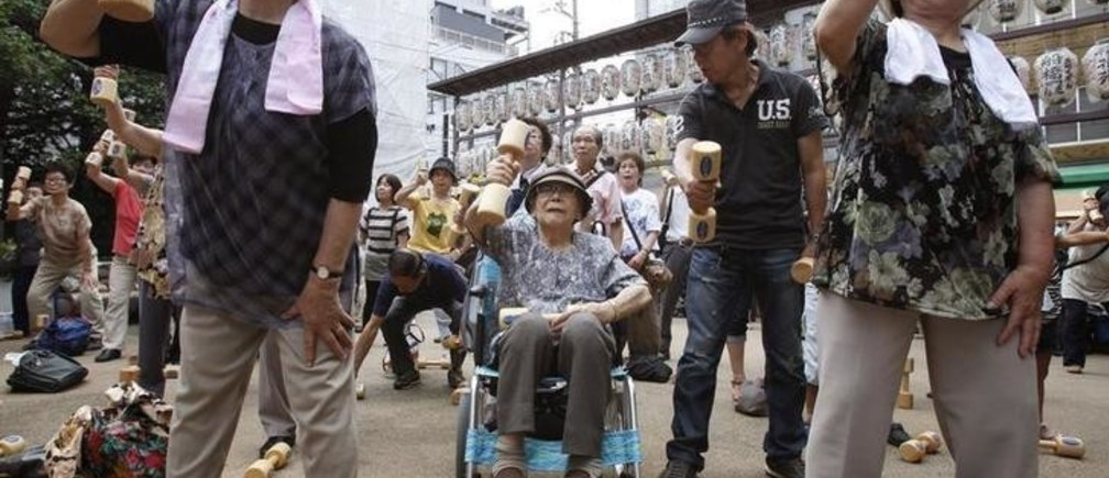 "Shizue Otori, 94-year-old, exercises with wooden dumbbells, amont other elderly people, during a health promotion event to mark Japan's ""Respect for the Aged Day"" at a temple in Tokyo September 19, 2011. Many elderly people took part in the event held at Sugamo district, where it is known as ""Harajuku for Grannies.""  REUTERS/Yuriko Nakao (JAPAN - Tags: HEALTH SOCIETY)"