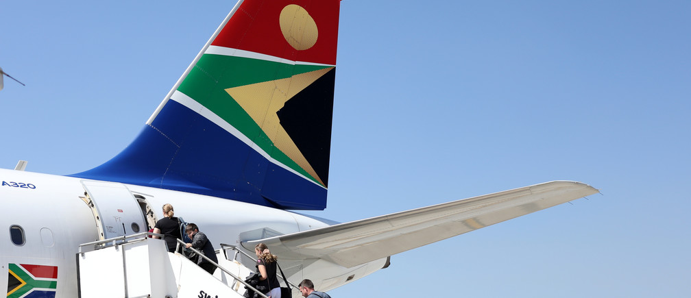 Passengers board a South African Airways plane at the Port Elizabeth International Airport in the Eastern Cape province, South Africa, September 30, 2018. REUTERS/Siphiwe Sibeko - RC19284257E0