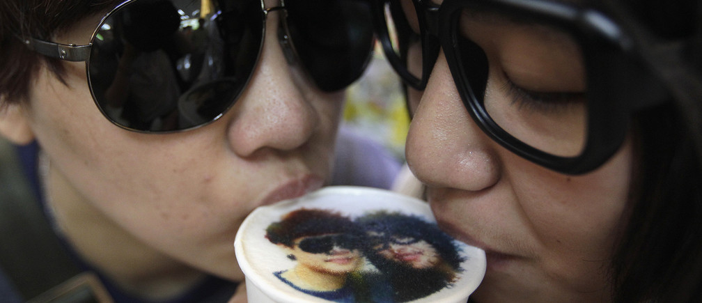 A couple drinks a cup of latte with their picture printed on top of the milk foam at a Family Mart in Taipei August 13, 2013. As part of Qixi Festival celebrations, customers of Family Mart's Let's Cafe were given the complimentary service of getting their pictures printed with edible inks on their lattes, according to a Family Mart employee. Qixi, also known as the Double Seventh Festival and the Chinese version of Valentine's Day, falls on the seventh day of the seventh month in the Chinese lunar calendar. REUTERS/Pichi Chuang (TAIWAN - Tags: ANNIVERSARY SOCIETY TPX IMAGES OF THE DAY) - GM1E98D17GF01