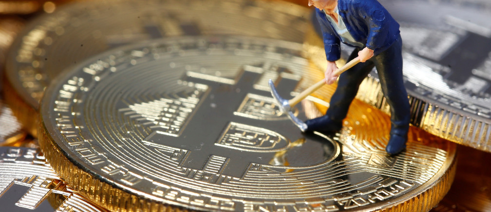 A small toy figure is seen on representations of the Bitcoin virtual currency in this illustration picture, December 26, 2017. REUTERS/Dado Ruvic/Illustration - RC18DE227180