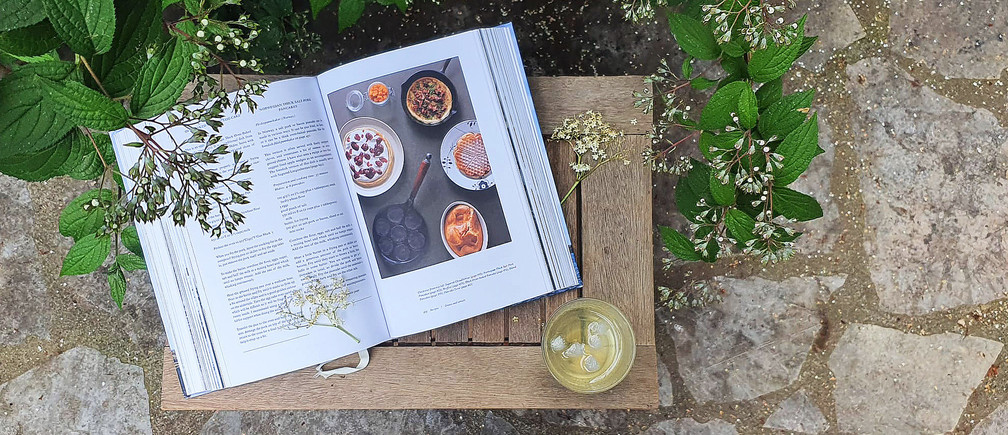 Magnus Nilsson's 'The Nordic Cookbook' is displayed to a recipe on a table outside