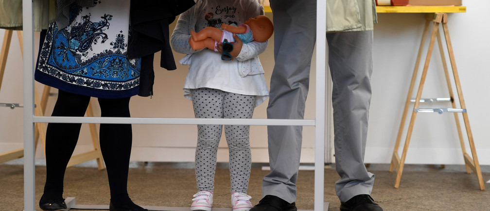 A girl and her parents are seen in one of the booths before voting during Spain's general election in Pola de Siero, April 28, 2019. REUTERS/Eloy Alonso - RC1749582090