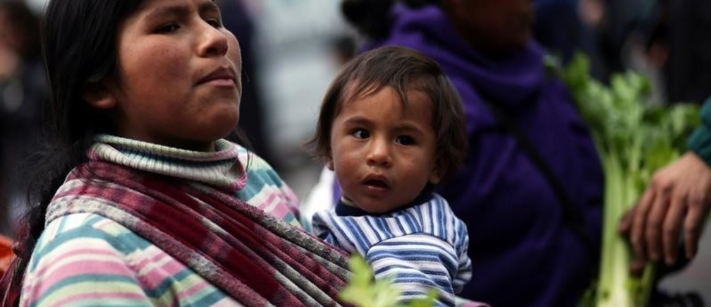 A vegetable grower carries a child as she arrives to Plaza de Mayo square to hand out products as a way of protesting price distortions and double-digit inflation they say crushes profits, in Buenos Aires, Argentina September 14, 2016.