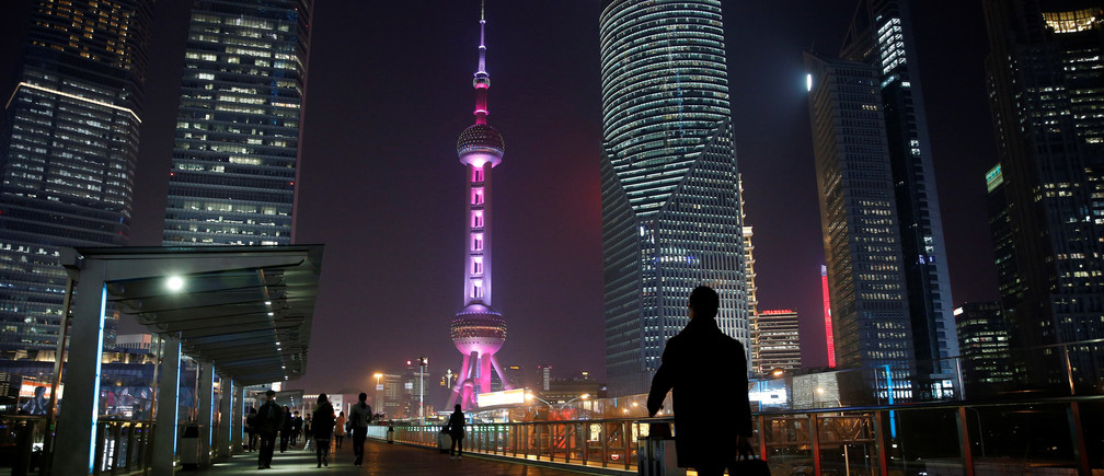 A man walks on a bridge in the financial district of Pudong in Shanghai, China.