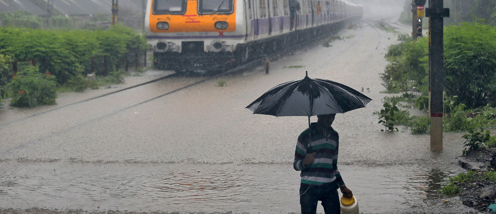 A man carrying an umbrella walks past a passenger train that moves through a water-logged track during heavy rains in Mumbai, India, July 9, 2018. REUTERS/Francis Mascarenhas