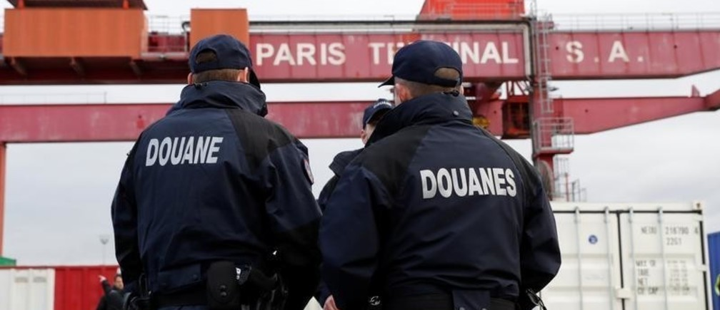 French customs officers stand next to a container during an anti-narcotics drill during the presentation of 2017 French customs results in the Port of Gennevilliers, near Paris, France March 13, 2018. REUTERS/Gonzalo Fuentes - RC1CE5E7FE90