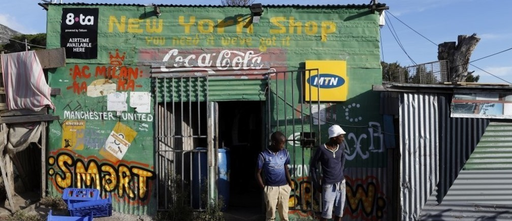 Residents stand outside a spaza convienience shop in Cape Town's Imizamo Yethu township, April 19, 2014