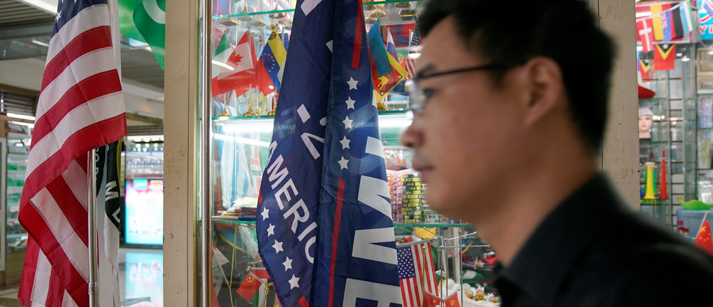"""A flag of the U.S. President Donald Trump's """"Keep America Great!"""" 2020 re-election campaign and the U.S. flag are seen in a flag stall at the Yiwu Wholesale Market in Yiwu, Zhejiang province, China, May 10, 2019. REUTERS/Aly Song - RC1C4FC93870"""