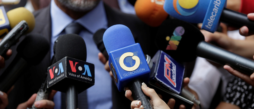 The logo of Globovision TV channel is seen on a microphone (C) used by a TV journalist among other microphones during a news conference in Caracas, Venezuela May 16, 2017. Picture taken May 16, 2017. REUTERS/Marco Bello - RTX37SFQ