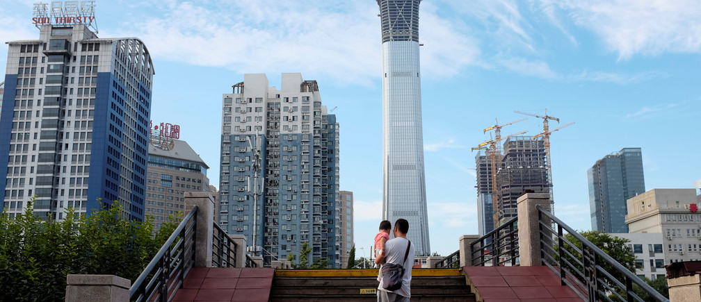 A man carrying a girl walks through a bridge at a park next to Beijing's central business area, China August 29, 2017. REUTERS/Jason Lee - RC1B3D140F40