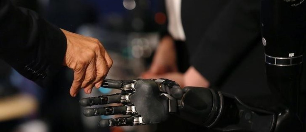 U.S. President Barack Obama touches a robotic arm operated by Nathan Copeland, a quadriplegic brain implant patient who can experience the sensation of touch and control a remote robotic arm with his brain during a tour of the innovation projects at the White House Frontiers conference in Pittsburgh, U.S. October 13, 2016.  REUTERS/Carlos Barria