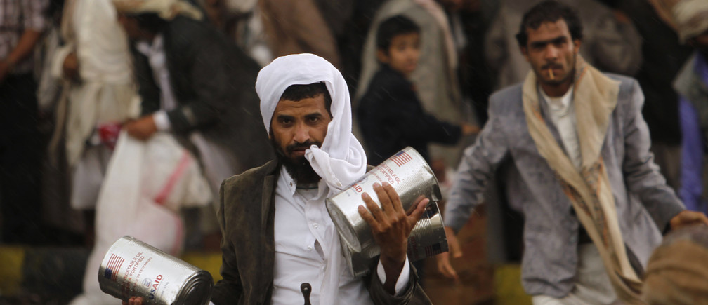 A Yemeni refugee carries cooking oil he received at a relief center in Sanaa