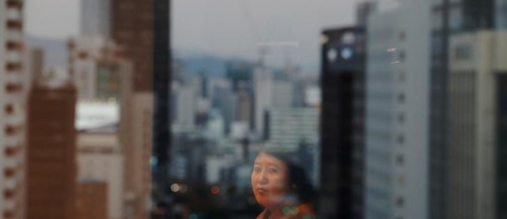 "Kim Ryen Hui, 48, is reflected on a window as she poses for a photograph in Seoul, South Korea, November 14, 2017. Ryon Hui is from Pyongyang. She says she never wanted to defect. In 2011, she says, a broker helped her go to China for treatment on her liver. But the broker tricked her, she said, and she ended up in South Korea. She is campaigning to return, which Seoul says would be against the law. ""I miss my parents even more than I miss my daughter. They're everything to me. For the first few years, I couldn't even breathe properly when I thought of them. My little brother lives with them in Pyongyang now. My mother can't see out of one eye. The thing I fear the most is finding out they've passed away before I have the chance to go back. My daughter and I have been writing letters and sending photos to each other. My cousin lives in China, so she's been sending them on. My daughter's name is Ri Ryon Gum. She was born on February 15, 1993. I don't want her to live out her life with me here. When she was young, she did taekwondo. She wanted to get involved in espionage operations against South Korea. She was so fearless. That's why she was doing taekwondo - to get involved in anti-South espionage. So I was really surprised to hear she became a chef. In a video of her I received, she explained why. She said that after I had left, she moved in with her father in Pyongyang and had been cooking for him. She said she decided to become a chef so she could fulfill my role at home. I was sad when I heard that."" REUTERS/Kim Hong-ji  SEARCH ""DEFECTORS"" FOR THIS STORY. SEARCH ""WIDER IMAGE"" FOR ALL STORIES."