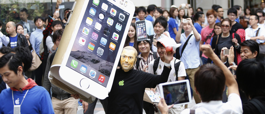 A man wearing a mask depicting Apple's co-founder Steve Jobs holds up a cardboard cut-out of Apple's new iPhone 6, as he walks into the Apple Store at Tokyo's Omotesando shopping district September 19, 2014.