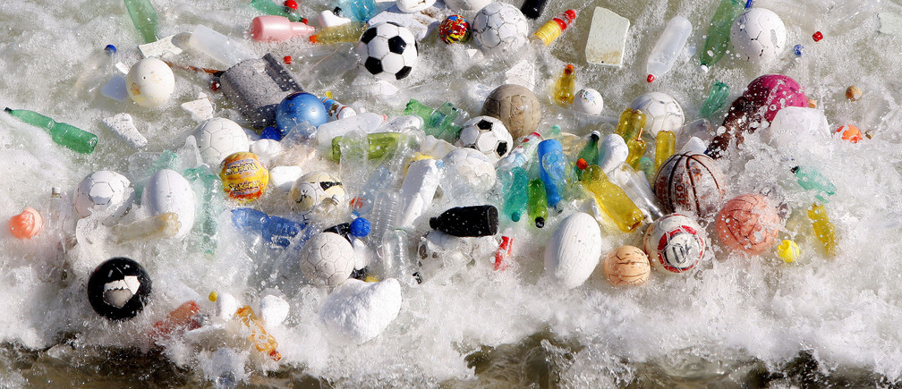Sports balls, and plastic bottles and other litter is accumulated by currents in the Tiber River in central Rome February 15, 2008. REUTERS/Alessandro Bianchi (ITALY) - GM1DXGSUSLAA