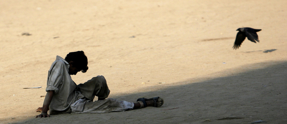 An unemployed migrant worker sits on a ground in Mumbai November 24, 2008. Thousands of migrants, mostly from north India,  come to Mumbai every year seeking casual labour. Due to the lack of employment and low wages, alcoholism, drug abuse and quarrels over money sharing is rampant among the migrants, who usually end up being homeless