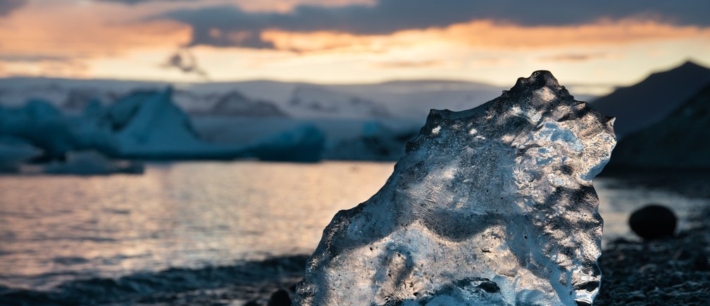 A segment of glacial ice slowly melts on the cold beach of a glacial lagoon in Iceland. permafrost thaw global warming carbon emissions