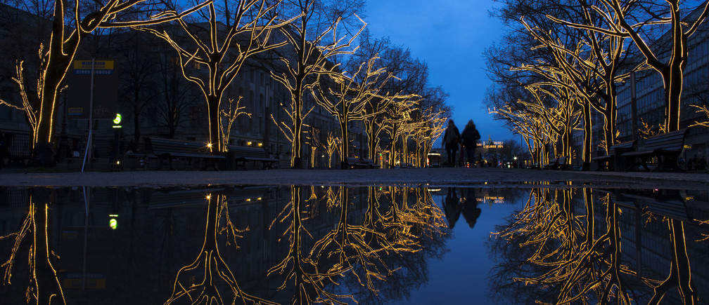 Trees decorated with Christmas lights are reflected in a puddle as people walk along the Unter den Linden promenade in Berlin November 28, 2012.