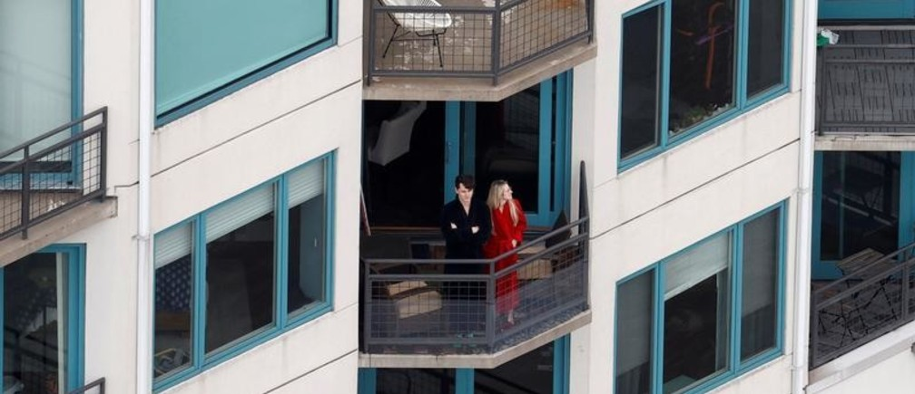 People stand on their balconies in an apartment building in New Jersey overlooking the Hudson River during the outbreak of coronavirus disease (COVID-19) in New York City, U.S., March 30, 2020. REUTERS/Mike Segar     TPX IMAGES OF THE DAY - RC2GUF93G33J