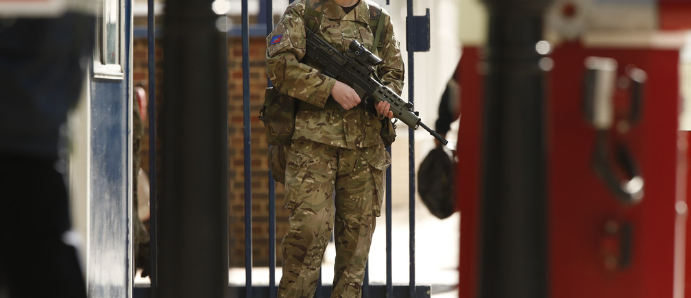 A female soldier stands outside the Royal Military Barracks, near the scene where a British soldier was killed in Woolwich, southeast London May 23, 2013.  The soldier was hacked to death on Wednesday by two men shouting Islamic slogans in a south London street, in what Prime Minister David Cameron said appeared to be a terrorist attack. REUTERS/Luke MacGregor   (BRITAIN - Tags: CRIME LAW MILITARY POLITICS SOCIETY) - LM1E95N0P0Y01