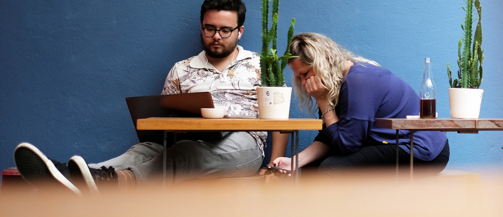 A man uses his computer next to a woman writing a message on her mobile phone at a cafe in Sao Paulo, Brazil October 17, 2017. REUTERS/Nacho Doce - RC1F35182670