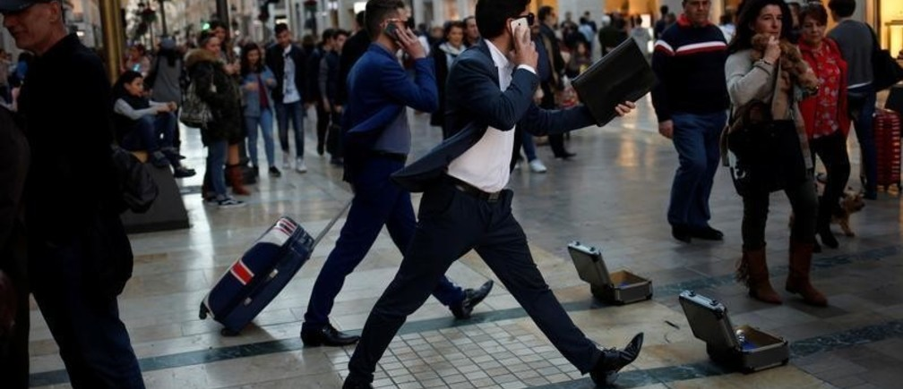 Street performers dressed up as businessmen perform as they ask for alms at Marques de Larios street in downtown Malaga, southern Spain January 3, 2018. REUTERS/Jon Nazca - RC1CC05C5E60