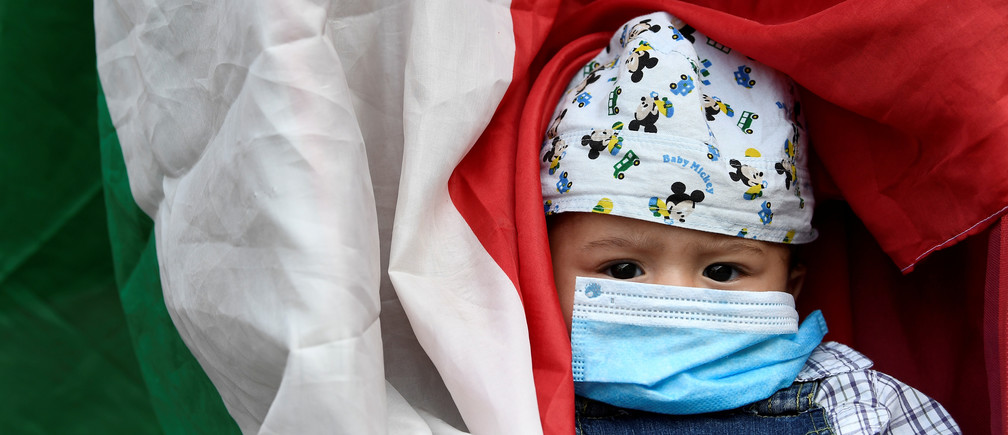 A child wearing a protective face mask is seen next to Italian flag during a protest in front of the town hall, as Italy eases some of the lockdown measures put in place during the coronavirus disease (COVID-19) outbreak, in Milan, Italy May 18, 2020. REUTERS/Flavio Lo Scalzo     TPX IMAGES OF THE DAY - RC2WQG9E3CZZ