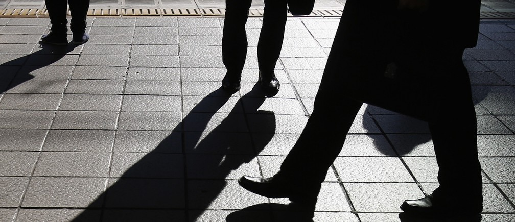 People stand on a platform at a train station in Tokyo December 8, 2014. Japan's economy shrank more than initially reported in the third quarter on declines in business investment, data showed on Monday, surprising markets and backing premier Shinzo Abe's recent decision to delay a second sales tax hike.