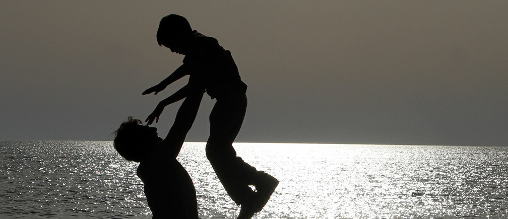 A father plays with his son on a beach facing the Adriatic sea, near the city of Durres, some 40 km (25 miles) from Tirana April 28, 2013.            REUTERS/Arben Celi (ALBANIA - Tags: SOCIETY) - GM1E94T0Q7F01