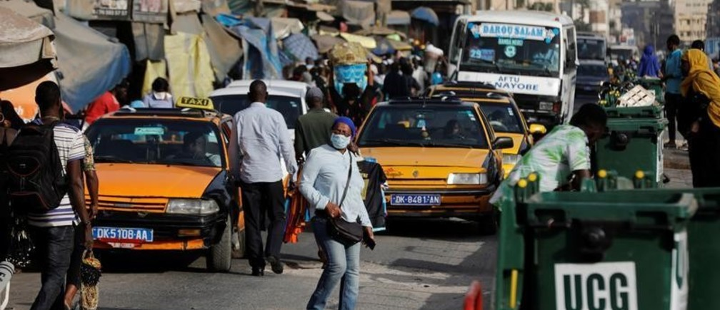 A woman wears a face mask, due to the global coronavirus disease (COVID-19) outbreak, as she walks along a busy shopping street in Dakar, Senegal March 18, 2020. Picture taken March 18, 2020. REUTERS/Zohra Bensemra - RC2VMF9P2N3C