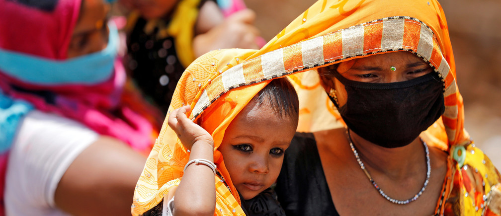 Migrant workers cover their children with saris, a traditional clothing worn by women, to protect them from heat as they wait to get on a bus to reach a railway station to board a train to their home state of eastern Bihar, during an extended lockdown to slow the spreading of the coronavirus disease (COVID-19), in Ahmedabad, India, May 20, 2020. REUTERS/Amit Dave - RC29SG9HFGRF