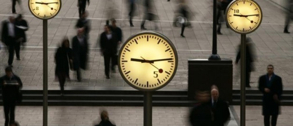 People walk past clocks at Reuters Plaza in London.