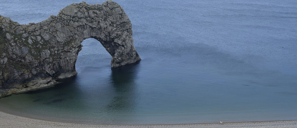 A couple walk their dog along the beach at Durdle Door with the English Channel sea connecting Britain to mainland Europe seen behind, in south west England, May 13, 2016.