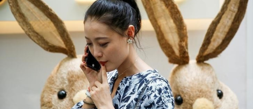 A woman talks on a mobile phone in Beijing, China June 3, 2017.   REUTERS/Thomas Peter