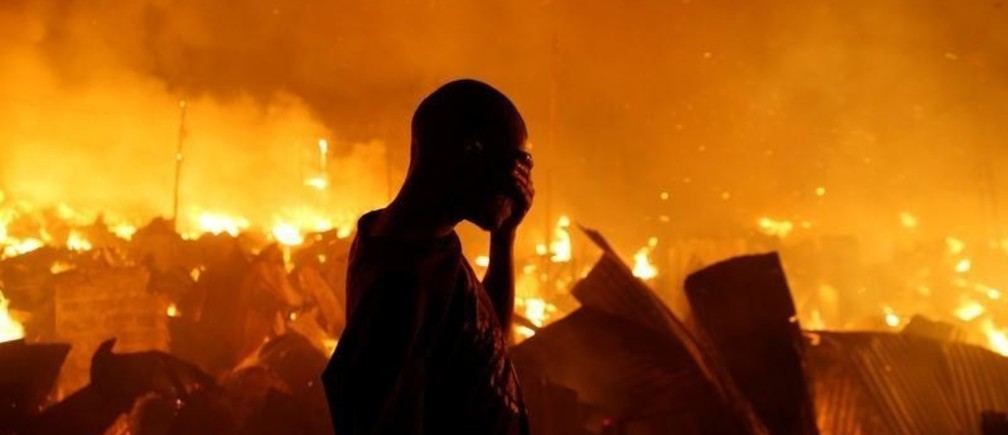 A resident reacts as he attempts to extinguish a fire that broke out at the Kijiji slums in the Southlands estate of Nairobi, Kenya, January 28, 2018. REUTERS/Thomas Mukoya     TPX IMAGES OF THE DAY - RC12FC043A10