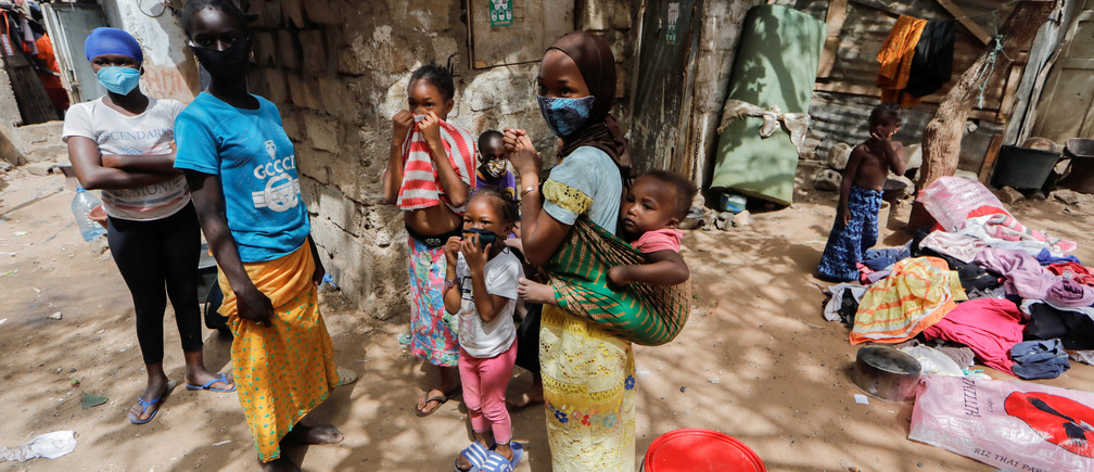 Children wearing face masks stand listening to their friends outside their shelters, amid the spread of the coronavirus disease (COVID-19), in Liberte 6 Baraka district of Dakar, Senegal May 2, 2020. REUTERS/Zohra Bensemra - RC2GGG93NMAL