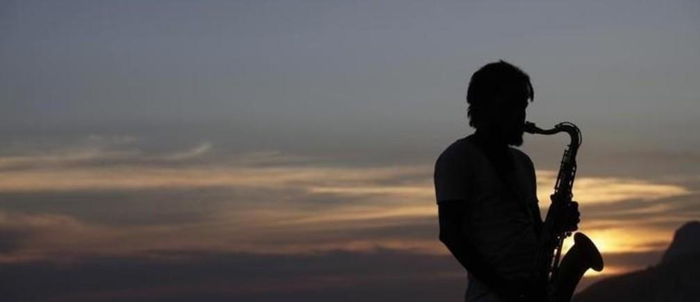 A musician plays saxophone at Arpoador beach as the sun sets in Rio de Janeiro February 12, 2010.   REUTERS/Ricardo Moraes (BRAZIL - Tags: SOCIETY)