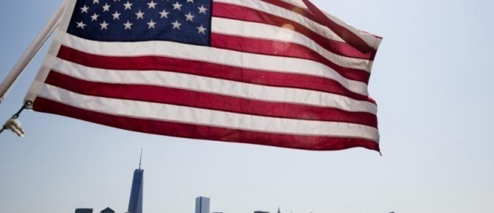 Image: A U.S. flag flies over the skyline of lower Manhattan in New York July 11, 2014. REUTERS/Lucas Jackson