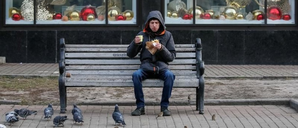 A man eats a sandwich and drinks a coffee as pigeons wait for the food in central Kiev, Ukraine January 27, 2020.  REUTERS/Gleb Garanich - RC2EOE9H2EUY