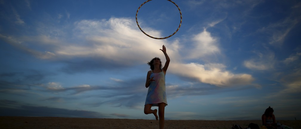 A woman plays with a hoop on Zikim beach in the Mediterranean sea near the southern Israeli city of Ashkelon February 18, 2016.