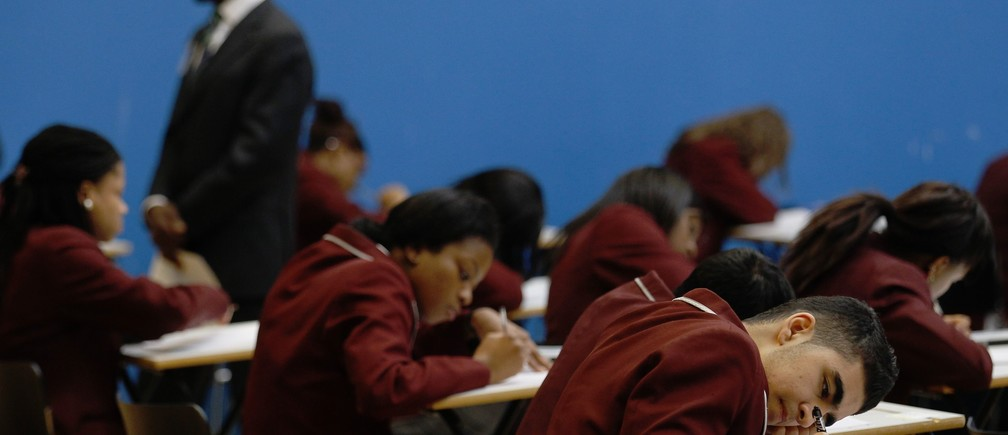 An invigilator monitors pupils during a GCSE mathematics exam at the Harris Academy South Norwood in south east London, March 2, 2012   REUTERS/Luke MacGregor