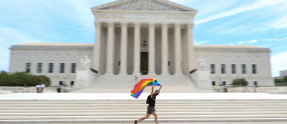 Joseph Fons holding a Pride Flag, runs in front of the U.S. Supreme Court building after the court ruled that a federal law banning workplace discrimination also covers sexual orientation, in Washington, D.C., U.S., June 15, 2020. REUTERS/Tom Brenner     TPX IMAGES OF THE DAY - RC2S9H9RU8J1