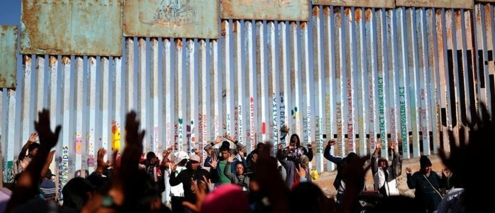 Migrants, part of a caravan of thousands trying to reach the U.S., pray by the border fence between Mexico and the United States, in Tijuana, Mexico November 15, 2018. REUTERS/Carlos Garcia Rawlins - RC19740C0490