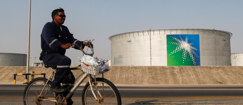 An employee rides a bicycle next to oil tanks at Saudi Aramco oil facility in Abqaiq, Saudi Arabia October 12, 2019. REUTERS/Maxim Shemetov - RC112617AD30