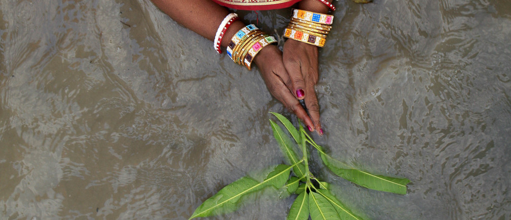 A Hindu woman performs ritual as she worships the Sun god on the banks of the river Ganges on the occasion of Chhat Puja in the eastern Indian city of Kolkata November 4, 2008. Hindu devotees fast all day for the betterment of their family and society during the festival and take a cleansing dip in the holy river Ganges. REUTERS/Jayanta Shaw (INDIA)   BEST QUALITY AVAILABLE - GM1E4B41UEB01