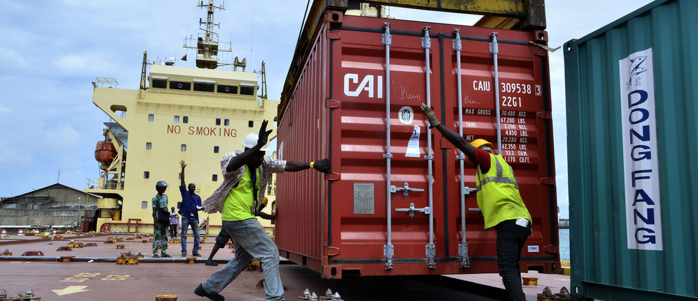 Workers move a container of rice onto a World Food Programme-operated ship at the port of Cotonou October 13, 2014.