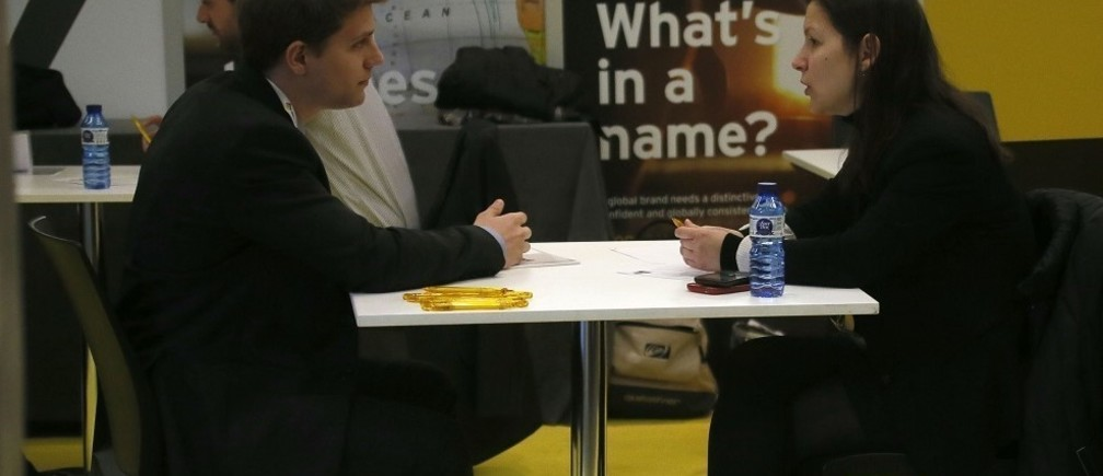 An attendee is interviewed by a company representative during the JOBarcelona'14 at the Palau de Congressos de Catalunya in Barcelona, February 18, 2014. JOBarcelona'14 is a two-day job fair targeted at university graduates.