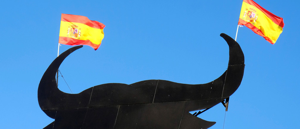 Spanish flags are attached to the horns of a billboard-size figure of a bull near Requena, Spain